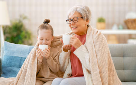 A nice girl and her grandmother enjoying warm beverages. Good time at home. Stok Fotoğraf
