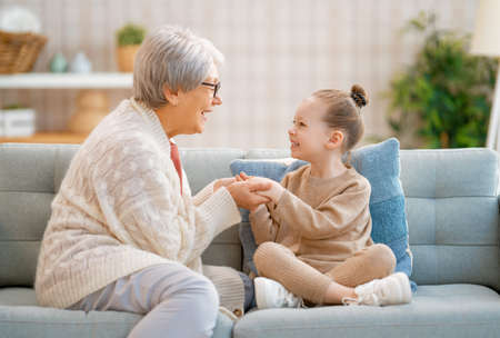 A nice girl and her grandmother enjoy sunny morning. Good time at home.