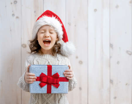 Happy little girl with Christmas gift on white wooden background.