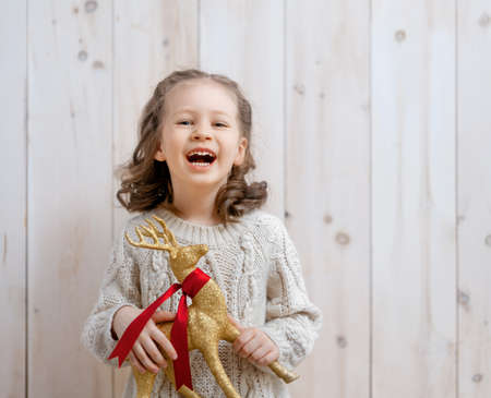 Happy little girl with Christmas reindeer on white wooden background. Stok Fotoğraf