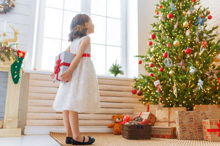 Merry Christmas and Happy Holidays! Cheerful cute child girl with gift. Kid is having fun near tree.