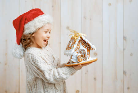 Happy little girl with Christmas gingerbread house on white wooden background.