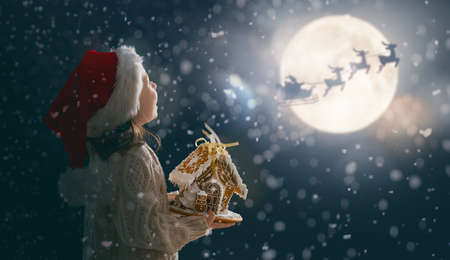 Merry Christmas! Cute little child with gingerbread house. Santa Claus flying in his sleigh against moon sky. Happy kid enjoy the holiday. Portrait of girl on dark background.