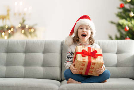 Merry Christmas and Happy Holidays! Cheerful cute child girl with gift. Kid is having fun near tree. Stok Fotoğraf