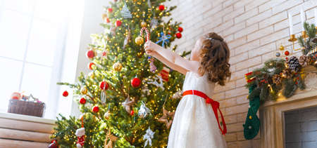 Merry Christmas and Happy Holidays! Cute little child girl is decorating the tree indoors. The morning before Xmas.