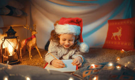Merry Christmas and Happy Holidays! Cute little child girl is writing the letter to Santa Claus near tree indoors.