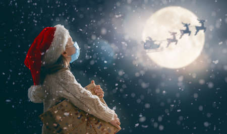 Merry Christmas! Cute little child with xmas present. Santa Claus flying in his sleigh against moon sky. Happy kid enjoy the holiday. Portrait of girl in face mask with gifts on dark background.