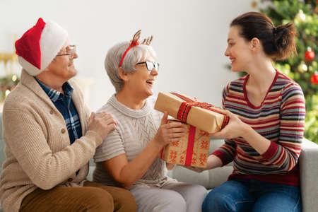 Merry Christmas and Happy Holidays! Senior mom, dad and their adult daughter exchanging gifts. Having fun near tree indoors. Loving family with presents in room. Stockfoto