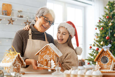 Merry Christmas and Happy Holidays. Family preparation holiday food. Grandmother and granddaughter cooking gingerbread house.