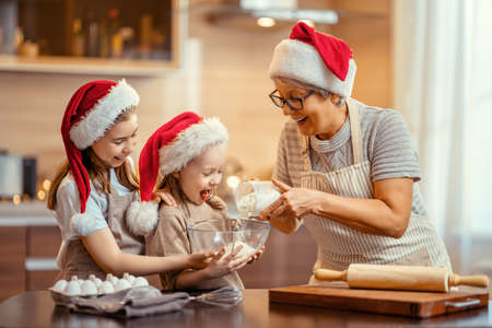 Merry Christmas and Happy Holidays. Family preparation holiday food. Grandma and granddaughters cooking cookies.