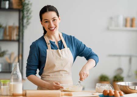 Happy woman is preparing bakery. Girls is cooking cookies in the kitchen. Homemade food. Stok Fotoğraf