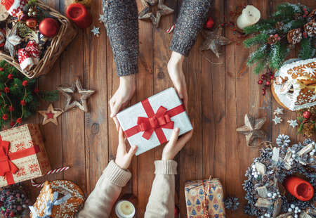 Merry Christmas and Happy Holidays! A man and woman with Xmas gift. Presents and hands. Top view. Xmas family traditions. Stok Fotoğraf