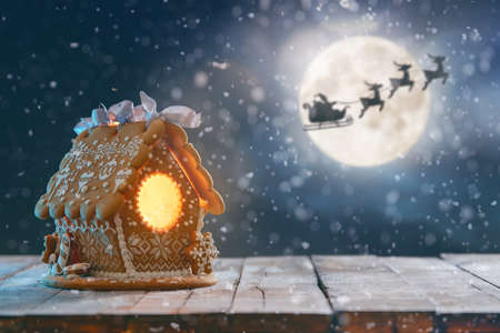 Merry Christmas and Happy Holidays! Gingerbread house on wooden table. Xmas night. Santa Claus flying in his sleigh against moon sky.