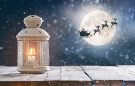 Merry Christmas and Happy Holidays! Lantern on wooden table. Xmas night. Santa Claus flying in his sleigh against moon sky.
