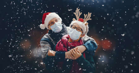 Merry Christmas! Winter portrait of senior couple on snowy dark background. People wearing facemasks. Imagens - 160001053