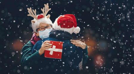 Merry Christmas! Winter portrait of senior couple on snowy dark background. People wearing facemasks. Imagens