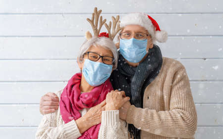 Merry Christmas and Happy Holidays! Winter portrait of loving senior couple on white wooden background. People wearing facemasks. Imagens - 160001055
