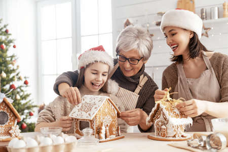 Merry Christmas and Happy Holidays. Family preparation holiday food. Grandma, mother and daughter cooking ginger house. Stockfoto