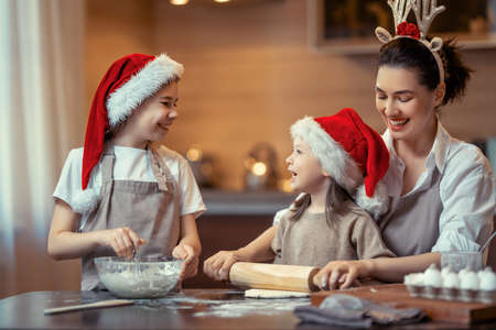 Merry Christmas and Happy Holidays. Family preparation holiday food. Mother and daughters cooking cookies. Imagens - 160001058
