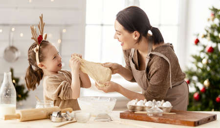 Merry Christmas and Happy Holidays. Family preparation holiday food. Mother and daughter cooking cookies. Imagens - 160147881