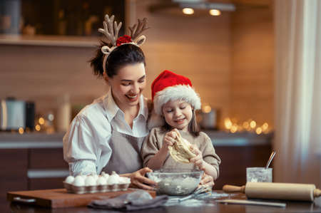 Merry Christmas and Happy Holidays. Family preparation holiday food. Mother and daughter cooking cookies. Imagens - 160147882