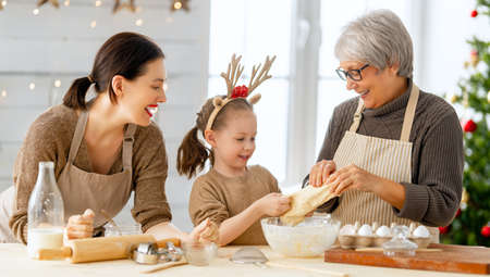 Merry Christmas and Happy Holidays. Family preparation holiday food. Grandma, mother and daughter cooking cookies. Imagens - 160147885