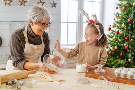 Merry Christmas and Happy Holidays. Family preparation holiday food. Grandma and granddaughter cooking cookies. Imagens