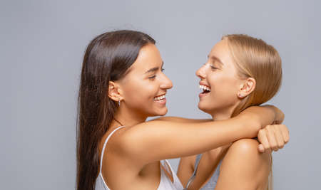 Portrait of two young women standing together and hugging. Imagens - 162129782