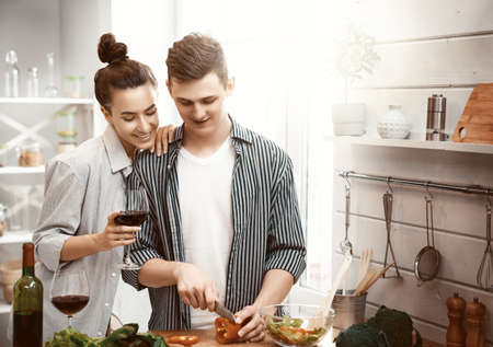 Healthy food at home. Happy loving couple is preparing the proper meal in the kitchen. Imagens