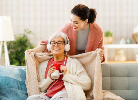 Beautiful mother and daughter are smiling while sitting on couch at home. Imagens