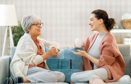 Beautiful mother and daughter are talking and smiling while sitting on couch at home. Imagens - 161889062