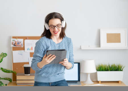 Happy casual beautiful woman working on a tablet pc in home office. Imagens - 161889067