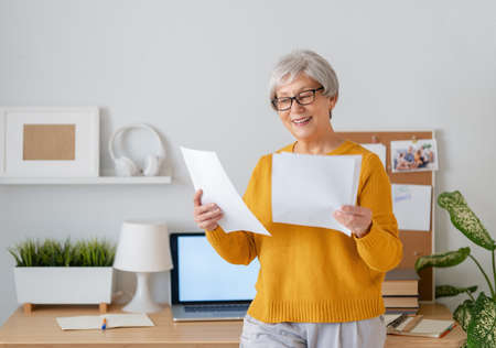 Happy casual senior woman working on a laptop at home. Imagens