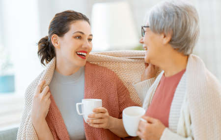 Beautiful mother and daughter are talking and smiling while sitting on couch at home. Imagens - 161889075