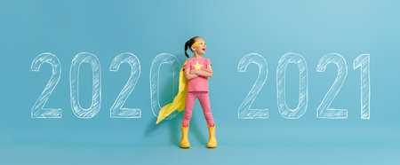 Child in superhero costume between 2020 and 2021 years on background of wall. Imagens - 161898328