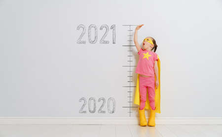 Child in superhero costume between 2020 and 2021 years on background of wall.
