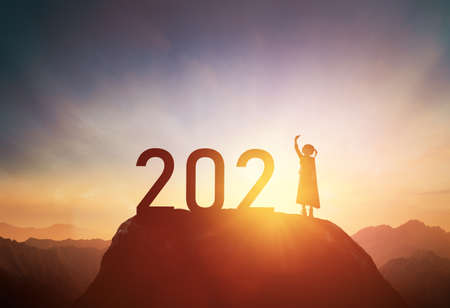 Silhouette of a child standing on the mountain with 2021 against the sunset, the concept of a successful New year.