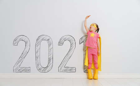 Child in superhero costume near 2021 years on background of wall.