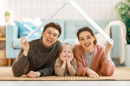 Mother, father and child girl in the room with a symbol of roof. Concept of housing for young family. Imagens - 161898337