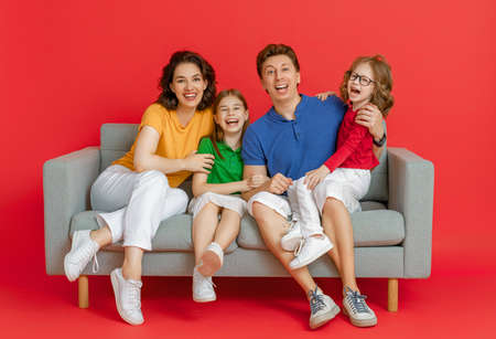Happy loving family. Mother, father and children daughters on red background. Imagens - 161898338