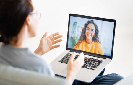 Young woman is using laptop for remote conversation with friend. People having fun staying at home. Imagens - 161898339