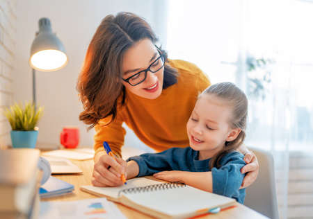 Happy child and adult are sitting at desk. Girl doing homework or online education.