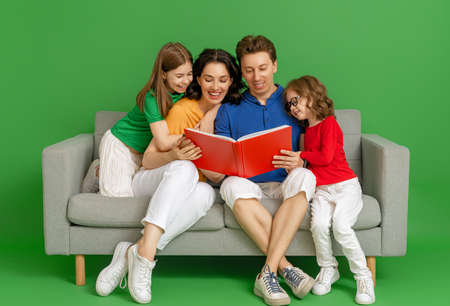 Happy loving family. Mother, father and children daughters reading a book on green background. Imagens