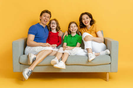 Happy loving family. Mother, father and children daughters on yellow background.