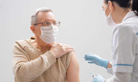 Doctor giving a senior man a vaccination. Virus protection. COVID-2019.