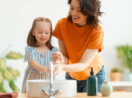 A cute little girl and her mother are washing their hands. Protection against infections and viruses. Imagens - 161898376