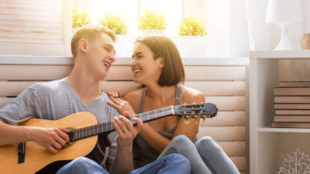 Happy couple in love. Stunning sensual portrait of young stylish fashion couple indoors. Young man playing guitar for his beloved girl. Imagens - 161898383