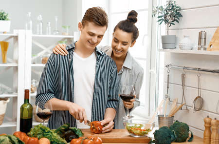 Healthy food at home. Happy loving couple is preparing the proper meal in the kitchen. Imagens - 161898385