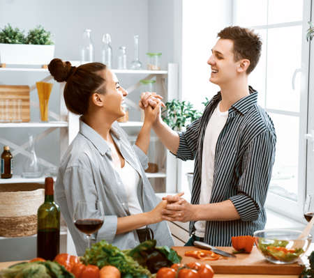 Healthy food at home. Happy loving couple is preparing the proper meal in the kitchen. Imagens - 161898391
