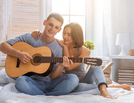 Happy couple in love. Stunning sensual portrait of young stylish fashion couple indoors. Young man playing guitar for his beloved girl. Imagens - 161898400